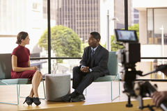Чернокожий человек и белая женщина на комплекте снимая интервью ТВ стоковое фото rf