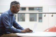 Чернокожий человек постаретый серединой используя компьтер-книжку, конец вверх по взгляду со стороны Стоковые Фотографии RF