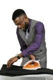 Чернокожий человек с утюгом одежд Стоковая Фотография