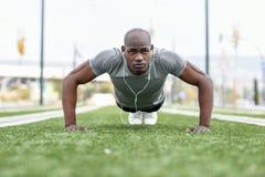 Чернокожий человек фитнеса работать нажимает поднимает в городской предпосылке стоковая фотография