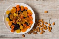 Черносливы, высушенные абрикосы, высушенные мандарины и миндалины в шаре на светлой деревянной предпосылке Стоковая Фотография