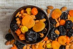 Черносливы, высушенные абрикосы, высушенные мандарины и миндалины в шаре на светлой деревянной предпосылке Стоковое Изображение RF
