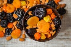 Черносливы, высушенные абрикосы, высушенные мандарины и миндалины в шаре на светлой деревянной предпосылке Стоковые Фотографии RF