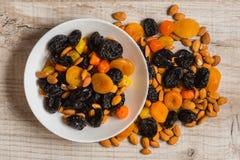 Черносливы, высушенные абрикосы, высушенные мандарины и миндалины в шаре на светлой деревянной предпосылке Стоковое Фото