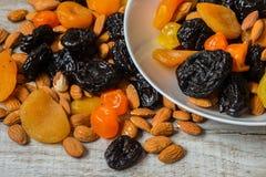 Черносливы, высушенные абрикосы, высушенные мандарины и миндалины в шаре на светлой деревянной предпосылке Стоковая Фотография RF