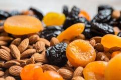 Черносливы, высушенные абрикосы, высушенные мандарины и миндалины на светлой деревянной предпосылке Стоковая Фотография