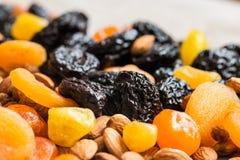 Черносливы, высушенные абрикосы, высушенные мандарины и миндалины на светлой деревянной предпосылке Стоковое Изображение RF