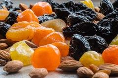 Черносливы, высушенные абрикосы, высушенные мандарины и миндалины на светлой деревянной предпосылке Стоковое Изображение