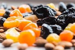Черносливы, высушенные абрикосы, высушенные мандарины и миндалины на светлой деревянной предпосылке Стоковые Изображения