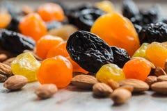 Черносливы, высушенные абрикосы, высушенные мандарины и миндалины на светлой деревянной предпосылке Стоковые Фотографии RF