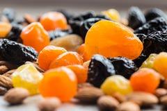 Черносливы, высушенные абрикосы, высушенные мандарины и миндалины на светлой деревянной предпосылке Стоковое фото RF