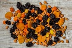 Черносливы, высушенные абрикосы, высушенные мандарины и миндалины на светлой деревянной предпосылке Стоковые Изображения RF