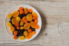 Черносливы, высушенные абрикосы и высушенные мандарины в блюде на светлой деревянной предпосылке Стоковые Фото