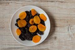 Черносливы и высушенные абрикосы в шаре на светлой деревянной предпосылке Стоковое Изображение