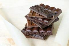 Чернота шоколадного батончика, milky, пористый шоколад штабелированный на пергаментной бумаге и деревянная доска День шоколада Стоковые Изображения