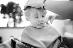 Черно-белая съемка мальчика preschooler получая стрижку Стоковое Фото