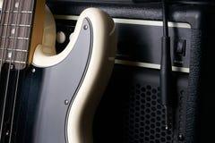 Черно-белая электрическая басовая гитара с кабелем jack и классическим усилителем Стоковая Фотография