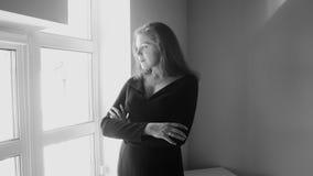 Черно-белое изображение молодой элегантной женщины смотря из большого окна Стоковые Фотографии RF