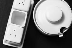 Черно-белое изображение шейкеров соли и перца, сахар-шара и держателя бумажной салфетки в деревянном столе Стоковое Изображение RF