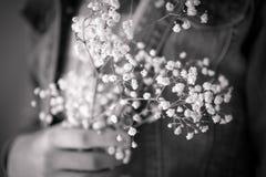 Черно-белое фото девушки держа дыхание ` s младенца цветет Стоковое Изображение