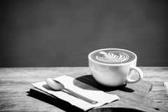 Черно-белый горячего искусства капучино кофейной чашки, ложки, ткани, прерывая доски на деревянном столе с космосом экземпляра Стоковое Изображение RF