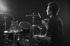 Черно-белая съемка барабанщика играя набор барабанчика в студии Стоковые Изображения