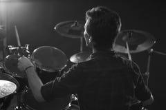 Черно-белая съемка барабанщика играя набор барабанчика в студии Стоковое фото RF