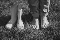 Черно-белая съемка девушки приняла ботинки и положение на gras Стоковые Изображения