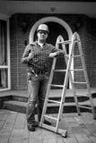 Черно-белая съемка работника представляя с инструментами на лестнице металла Стоковые Изображения RF