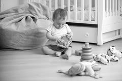 Черно-белое изображение младенца играя на поле с игрушками Стоковая Фотография