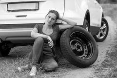 Черно-белое изображение унылой женщины распологая на землю на сломленном ca Стоковые Фото