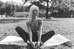 Черно-белое фото девушки спорт сидя на половике Стоковые Изображения RF