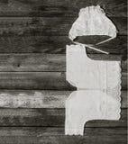 Черно-белое фото крышки и рубашки для newborn на старом деревенском крупном плане деревянного стола, взгляд сверху Стоковая Фотография RF