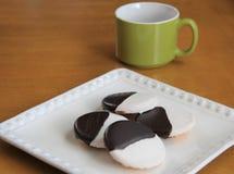 Черно-белые печенья на белой плите с чашкой кофе Стоковые Изображения