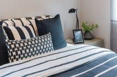 Черно-белые подушки и одеяло на кровати при включении черная лампа животики Стоковое Изображение RF