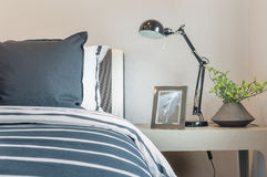Черно-белые подушки и одеяло на кровати при включении черная лампа животики Стоковое Фото