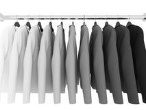 Черно-белые рубашки при вешалки изолированные на белизне Стоковое Изображение