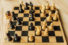 Черно-белые шахматные фигуры на доске во время игры Стоковое Изображение RF