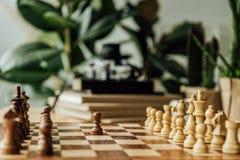 Черно-белые шахматные фигуры на шахматной доске готовой для того чтобы начать игру Стоковая Фотография