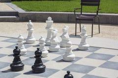 Черно-белые chessmen на доске улицы Стоковая Фотография