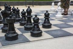 Черно-белые chessmen улицы с ногами женщины Стоковые Фото