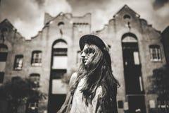 Черно-белый портрет милой усмехаясь девушки в солнечных очках с зданиями города на заднем плане Стоковые Фото