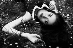 Черно-белый портрет молодой женщины лежа на траве с малыми цветками Взгляд сверху Стоковые Изображения