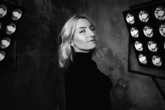 Черно-белый портрет молодой стильной красивой привлекательной курчавой девушки в черном свитере на этапе Стоковое Изображение RF