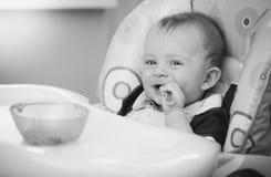Черно-белый портрет шаловливого младенца есть от ложки в высокой Стоковые Фото
