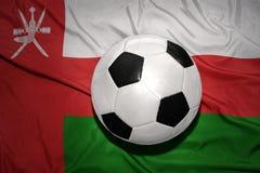 Черно-белый шарик футбола на национальном флаге Омана Стоковое Изображение RF