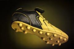 Черно- желтый ботинок футбола Стоковые Изображения