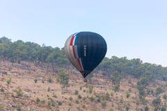 Черно- серый горячий воздушный шар летает вверх от земли на горячем фестивале воздушного шара Стоковые Фотографии RF