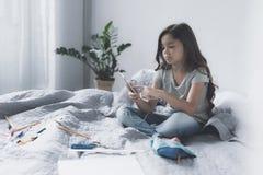 Черно-с волосами девушка в белых наушниках сидит на кровати при ее пересеченные ноги и слушает к музыке на сером smartphone Стоковые Фотографии RF