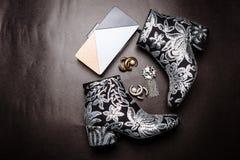 Черные ботинки лодыжки с толстыми пятками украшенными с цветками вышитыми с серебряными sequins и муфтой и фибулами металла на a стоковые фото